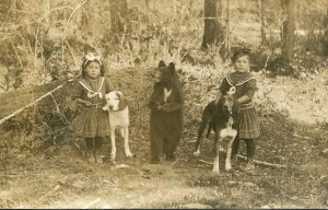 Clara and Bessie Jensen with stuffed bear and prized hunting dogs