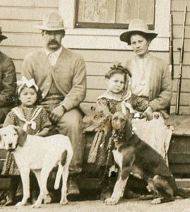 Clara and John Jensen with their daughters Clara (left) and Bessie (right) holding the hunting dogs.