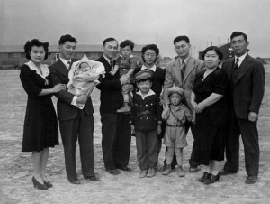 Left to right are, Mr. and Mrs. Howard Sakura and their baby, Frederick Scott Sakura, 10 weeks old; Chester is holding Jr., age 2; John David, age 7, is standing in front of Mrs. Chester Sakura; Gerald, 3-1/2, is in front of Kenny; Mrs. Misa Sakura, mother of the Sakura brothers; and Ted.  All the children, except the baby, belong to Chester.