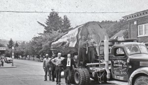 Men posing beside the Murphy Logging's tree on Mashell Ave.