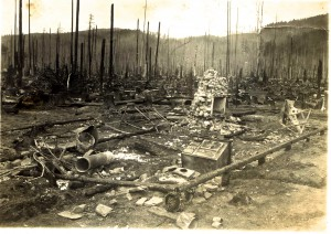 Japanese-American Millworkers standing on wreckage after the PNLC fire, May 13, 1912