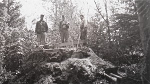 Men on the stump of the old growth tree.