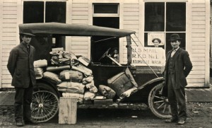 1913. Left: Postmaster Charles Williams. Right: Rural Carrier Fred Matheny. Background Mrs. Williams and Ray Williams.