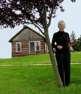 Jackie Van Eaton Parnell pictured with the cabin where it sits today (photo from Eatonville News.net)